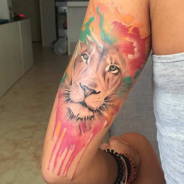 tattoo löwe, frau mit großer wassrfarben tattoo mit löwen-motiv am oberarm, aquarell