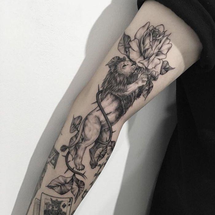 tattoo löwe, schwarz-graue tätowierung mit löwe und weißen rosen, arm tätowieren