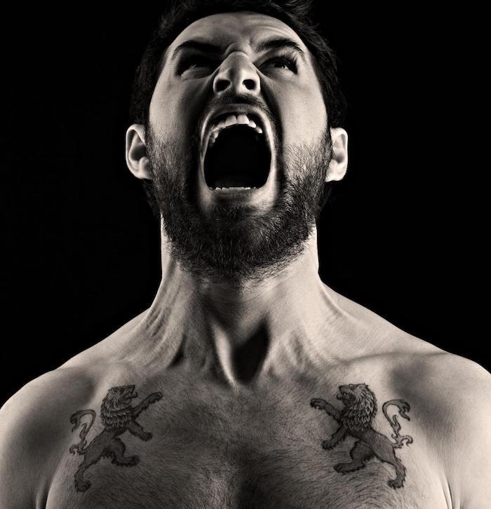 tattoo löwenkopf, mann mit zwei tätowierungen an der brust, schwarz-graue tattoos