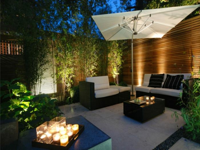 moderne terrassen am abend zum sitzen und entspannen, glas wein, bequemes sofa, kerzen, aromakerzen