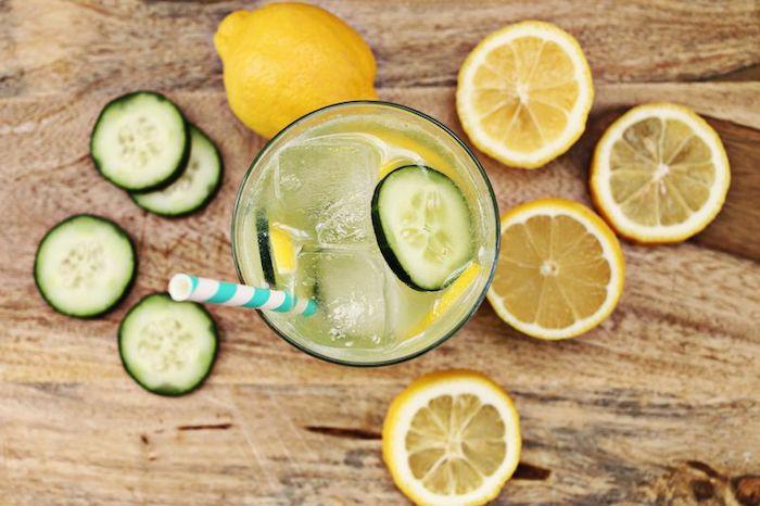 ein glas mit einer hausgemachten limonade mit grünen gurken und mit gelben zitronen und mit einem blauen strohhalm, ein tisch aus holz, amerikanische limonade rezept