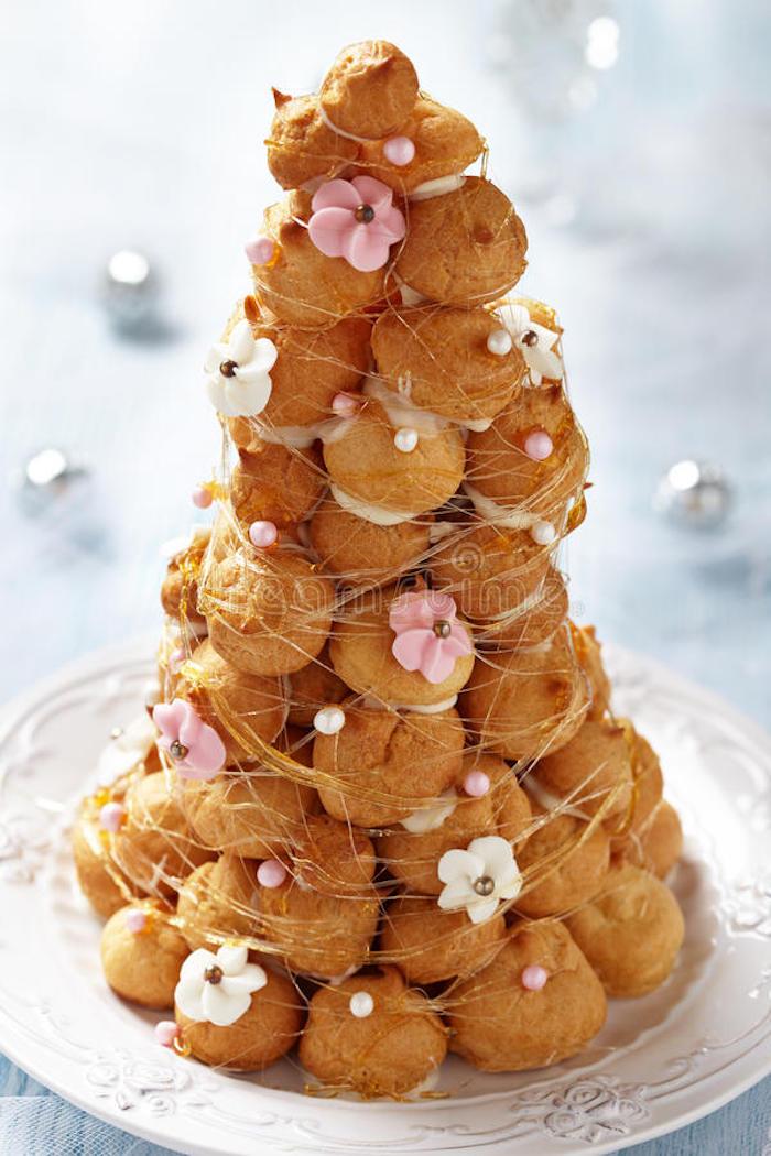torte aus süßigkeiten, großer weißer teller, geburtstagtorte aus kroketten dekoriert mit blümchen aus buttercreme und karamell