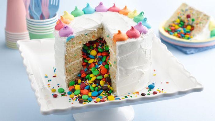 torte aus süßigkeiten, geburtstagskuchen-pinata gefüllt mit bunten bonbons, weiße sahne