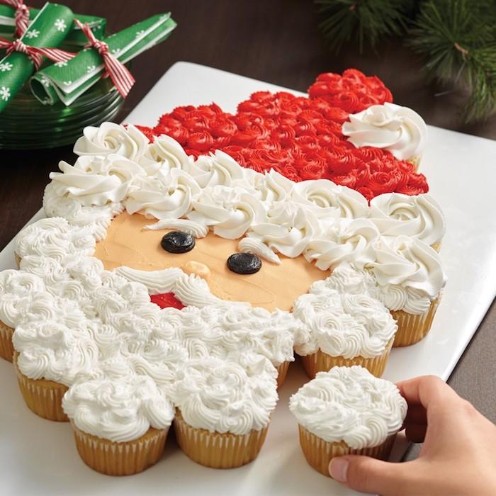 torte aus süßigkeiten für weihnachten, weihnachtsmann aus cupcakes, weiße und rote sahne