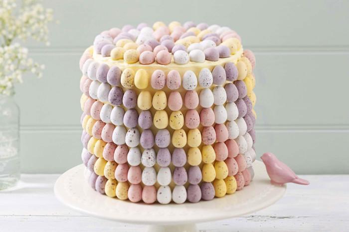 torte kinderschokolade, kuchen für ostern dekoriert mit vielen kleinen eiern, rosa vogel