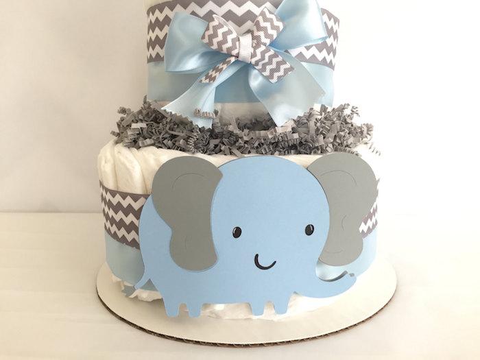 blauer großer elefant mit grauen ohren und kleinen schwarzen augen und eine torteaus weißen windeln und mit einer blauen schleife