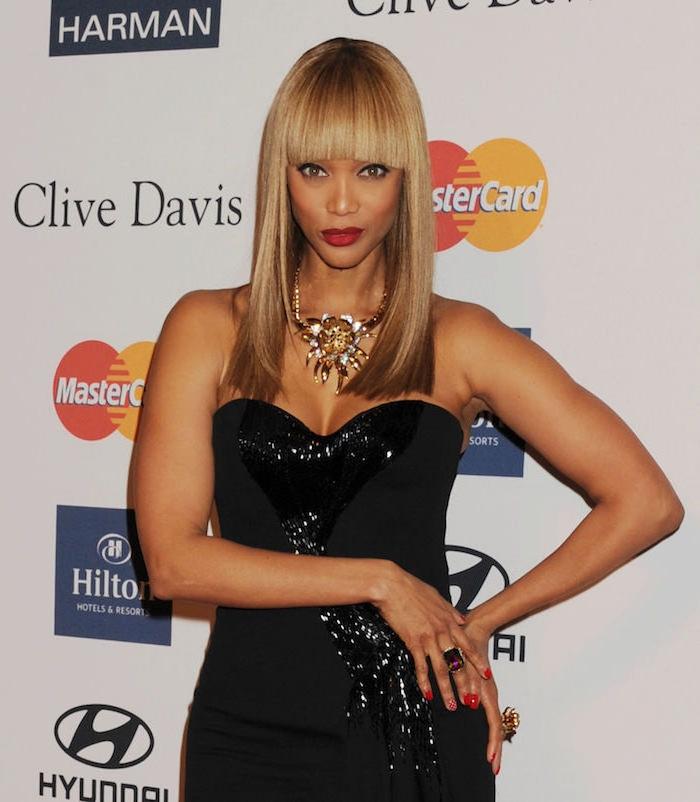 Tyra Banks Haarschnitt, dunkelblonde glatte Haare mit geradem Pony, trägerloses Abendkleid mit Kristallen, massive goldene Kette, roter Lippenstift