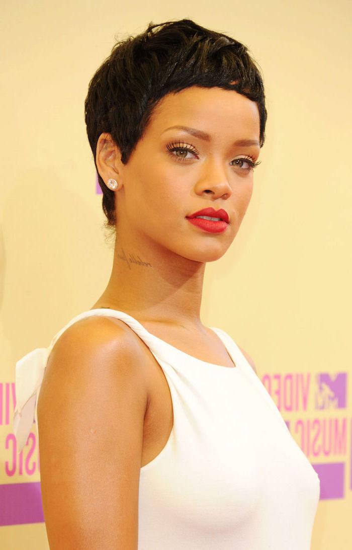 Rihanna Kurzhaarfrisur, schwarze Haare, roter Lippenstift und schwarze Mascara, weißes Top