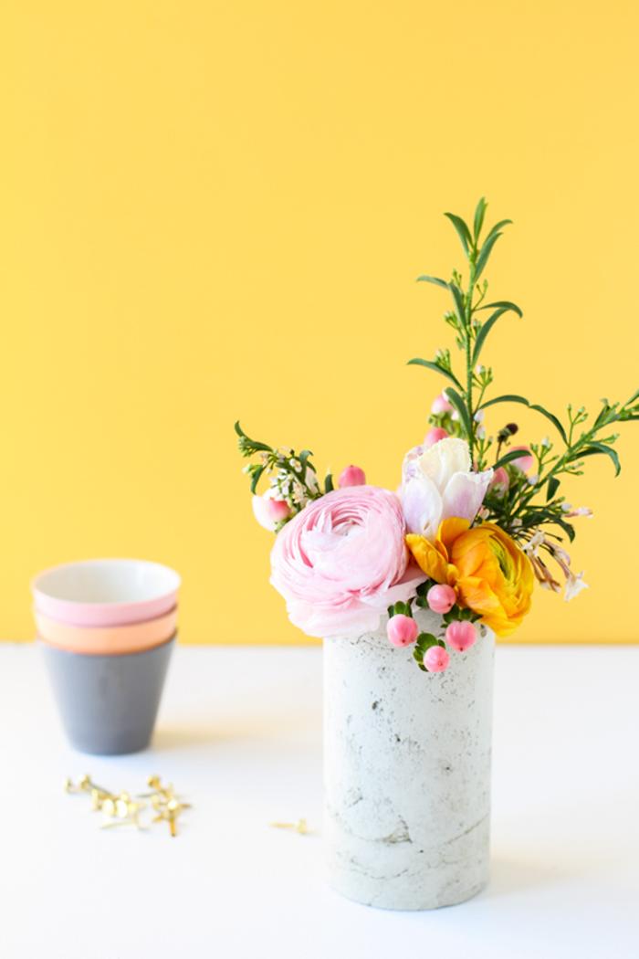Ranunkel in weißer Vase, kleiner Blumenstrauß für fröhliche Frühlingsstimmung zu Hause