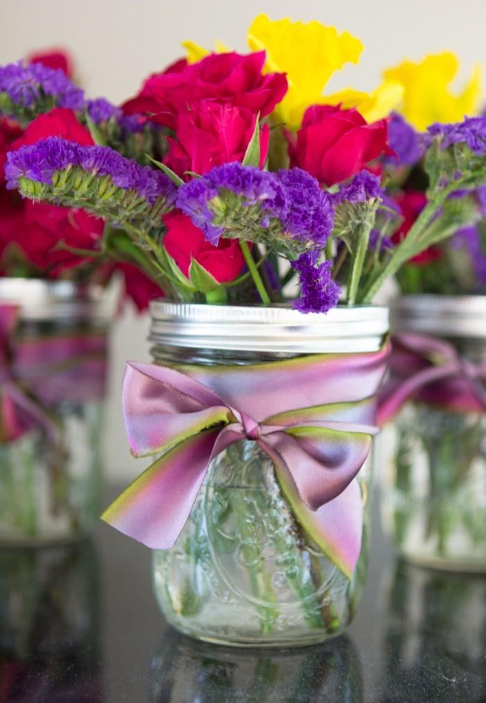 Vase aus Einmachglas selbst gestalten, mit lila Dekoband verzieren, kleiner Blumenstrauß