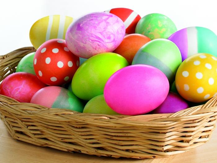 bunte Eier mit verschiedenen Techniken bemalt in rosa, grüner und roter Farbe bemalt