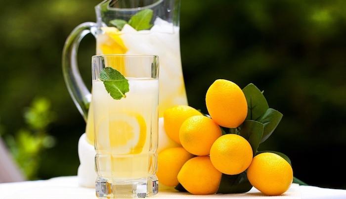 ein großer krug und ein glas mit vielen gelben zitronehn und mit eis und minze mit grünen blättern und einer gelben selbstgemachten limonade