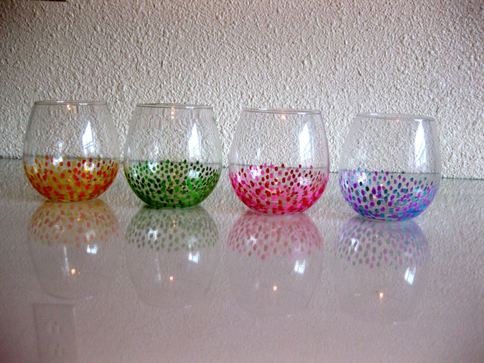 vier bunte Gläser, mit Wattenstäbchen Glas farben in grüner, oranger, rosa und blauer Farbe,