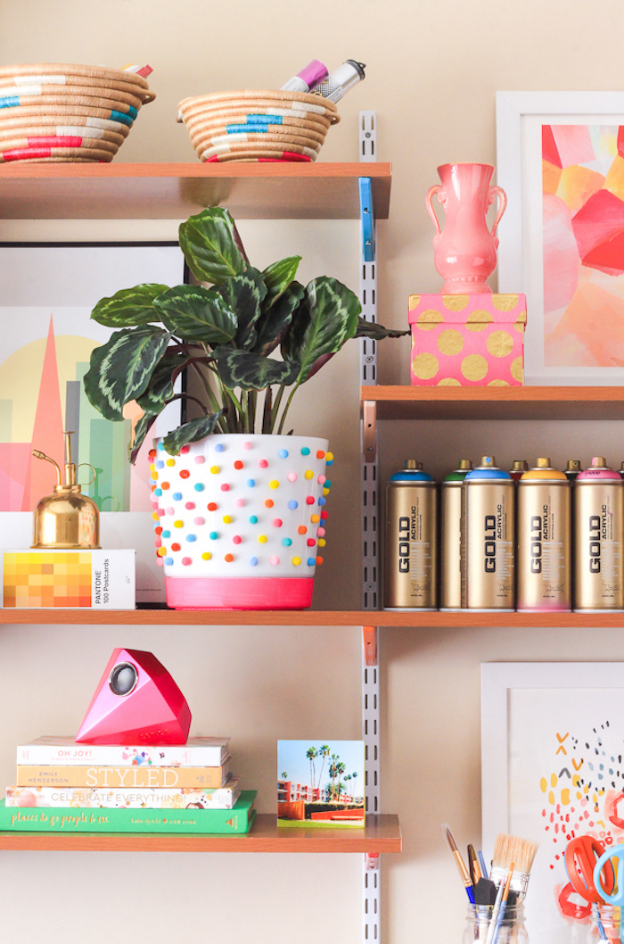 Selbst verzierter Blumentopf, grüne Zimmerpflanze, viele Sprays und Pinsel, Kunstwerke und Gemälde