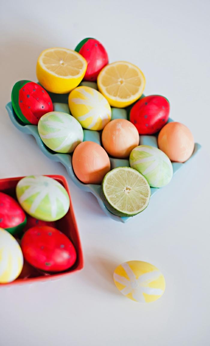 Erdbeeren, Zitronen, Limette und Apfel auf Eier anmalen und in Eierkaton ordnen