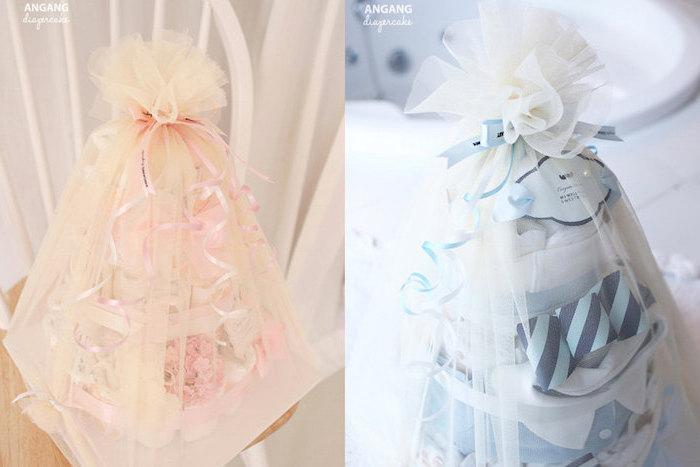 eine pinke windeltorte für mädchen und mit weißen windeln und pinken schleifen, eine torte mit blauen schleifen und weißen windeln