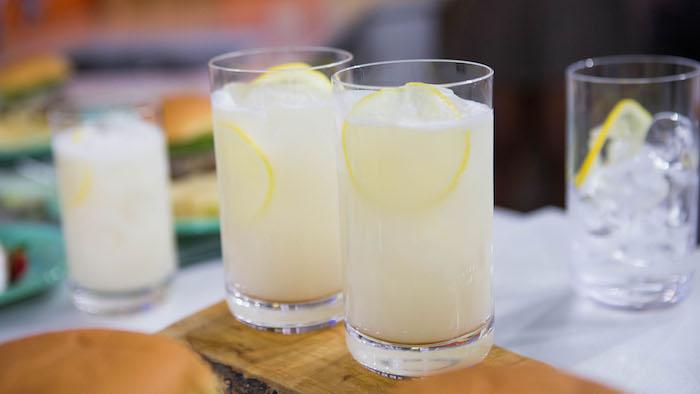 ein holzbrett und zwei gläser mit einer gelben selbstgemachten limonade mit zitronen und eis