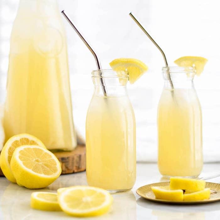 zwei große gläser mit einer selbstgemachten limonade mit eis und mit vielen gelben zitronen, ein holzbrett und ein großer krug mit einer gelben zitronnenlimonade
