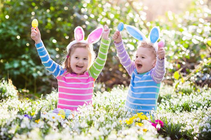 ein lustiges osterbild mit zwei mädchen mit gelben, blauen und pinken ostereiern und pinken und blauen hasenohren, ein garten mit vielen blumen und grünen pflanzen