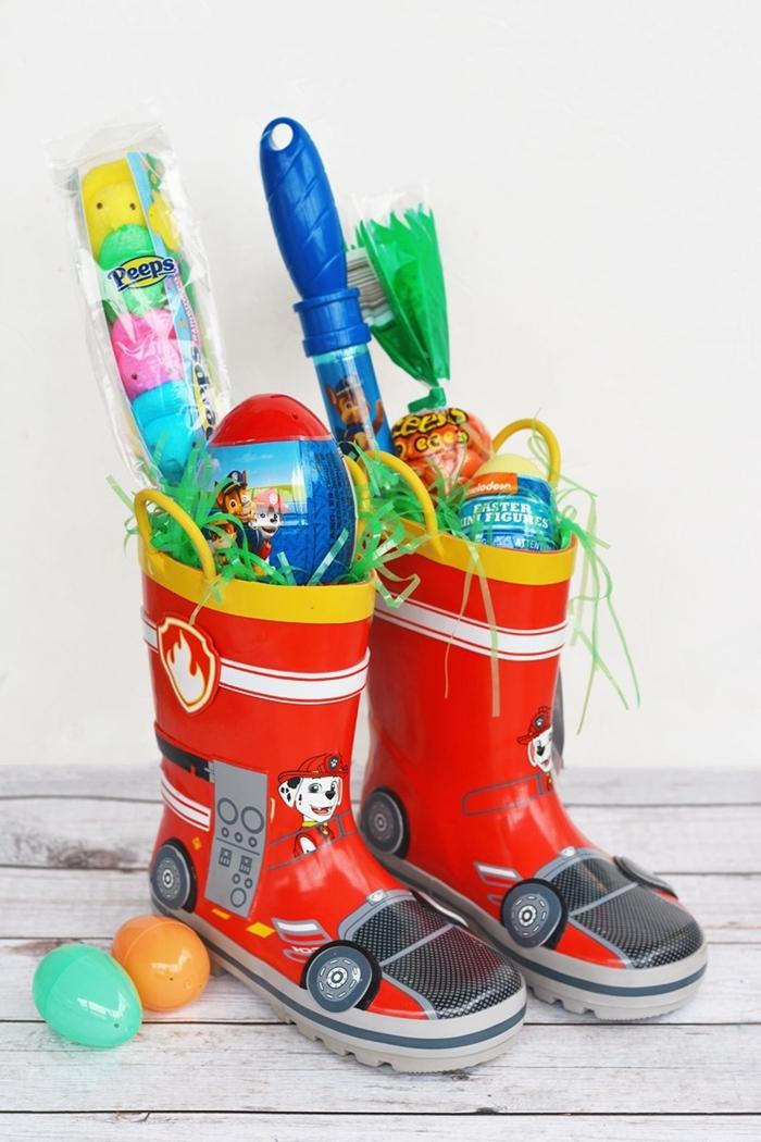 zwei Gummistiefel mit Spielzeuge und Süßigkeiten, kreative kleine Ostergeschenke