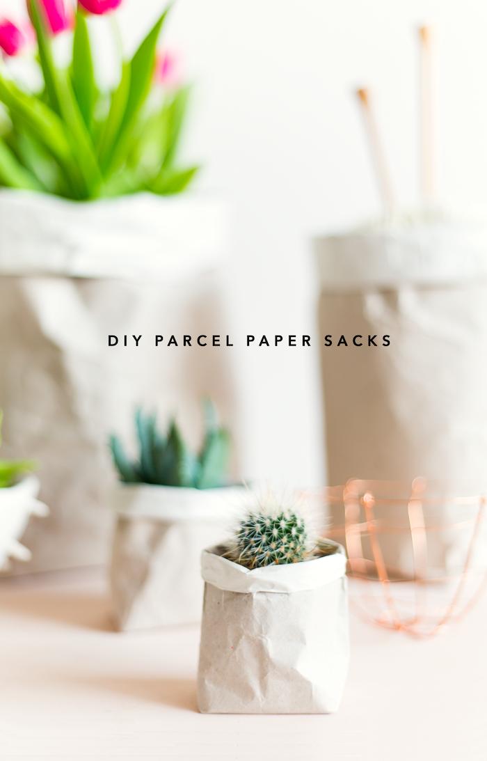 ein tisch und kleine weiße papiertüten mit violetten blumen mit grünen blättern und grünen pflanzen, basteln mit papier, papiertüten falten