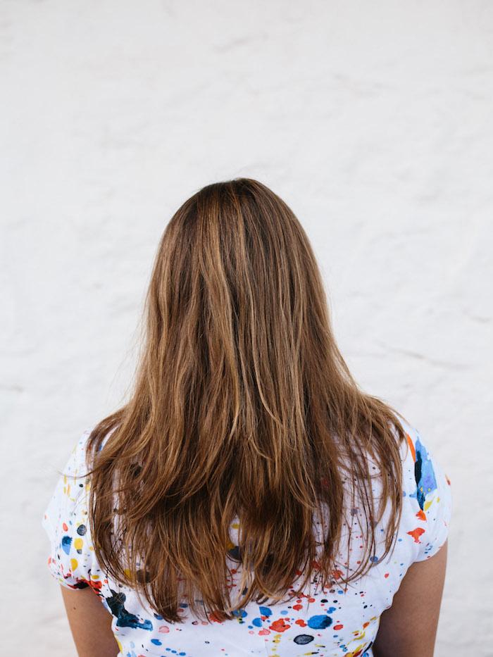 frisuren halblang gestuft locken, weißes t-shirt mit bunten punkten, braune haare mit blonden strähnen