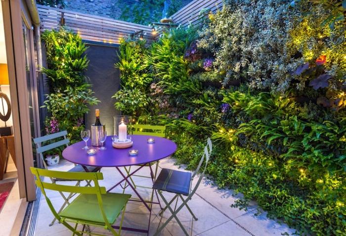 gartengestaltung beispiele, kleiner garten gestalten, wand mit grünen pflanzen, lila tisch, grüne stühle