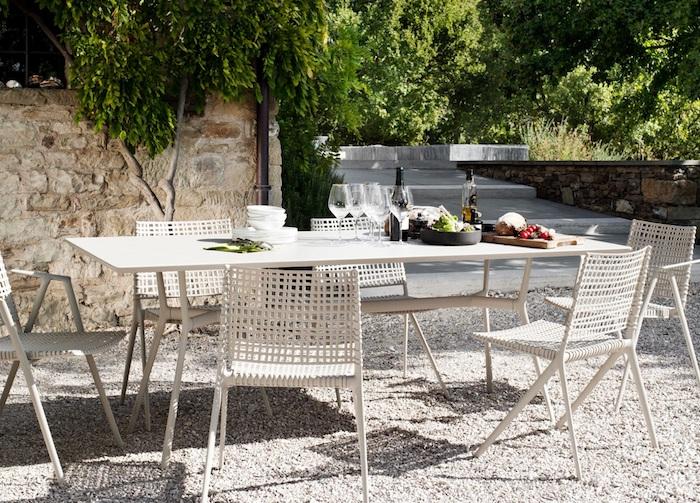 gartengestaltung beispiele, langer weißer tisch, stühle aus weißem ratan, weingläser, sitzecke