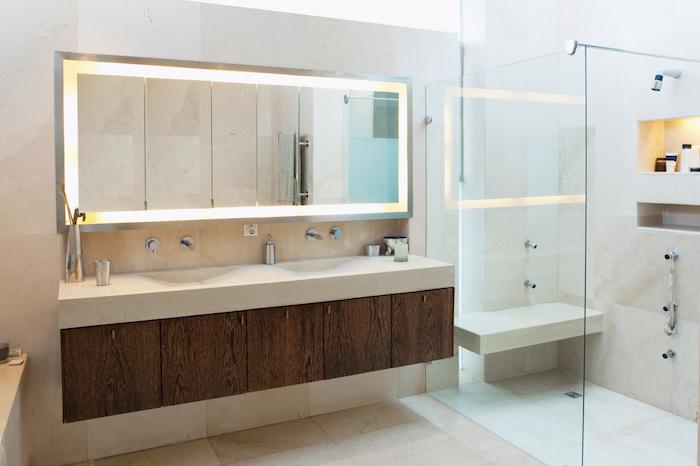 badezimmer mit einem großen spiegel und einmem waschbecken