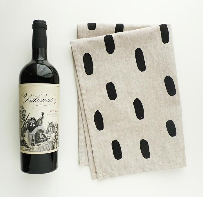 eine Weinflasche verpacken mit einem grauen Tuch auf schwarzen Flecken
