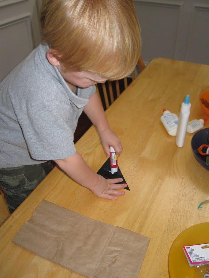 ein tisch aus holz und ein kleines kind mkit einem grauen t-shirt, eulen basteln, basteln mit papier und kleber, eine diy anleitung