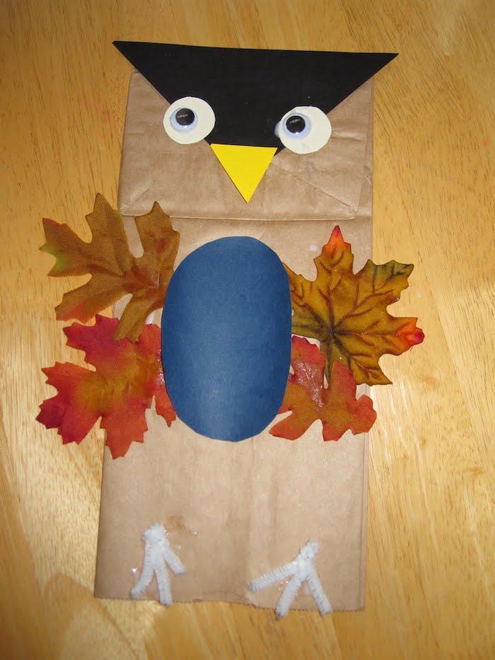 ein vogel aus einer alten braunen papiertüte und mit flügeln aus roten und braunen blättern, eulen basteln aus papier