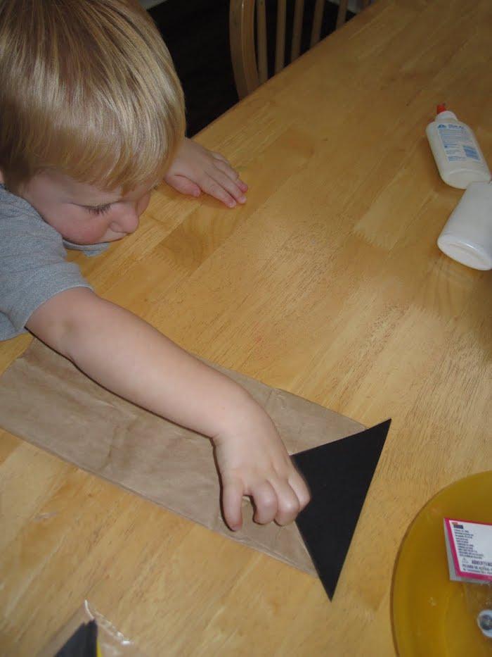 ein kleines kind und eine große tüte aus einem alten papier, basteln mit kindern, eulen basteln und papiertüten falten