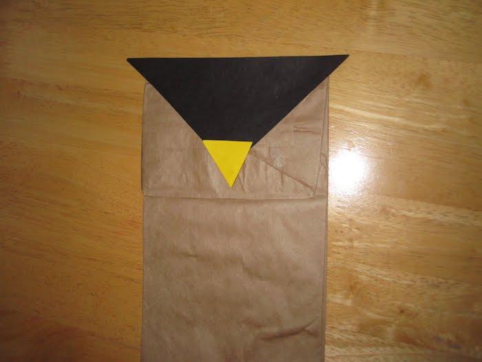 eine kleine braune eue aus einer alten braunen papiertüte und ein tisch aus holz, basteln mit kindern, eulen basteln aus papiertüten