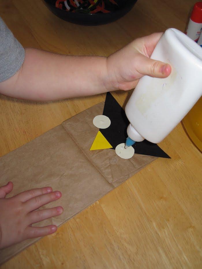 kleber und ein tisch aus holz, eine kleine braune eule aus einer braunen papiertüte, eine eule mit großen weißen augen, basteln mit papier