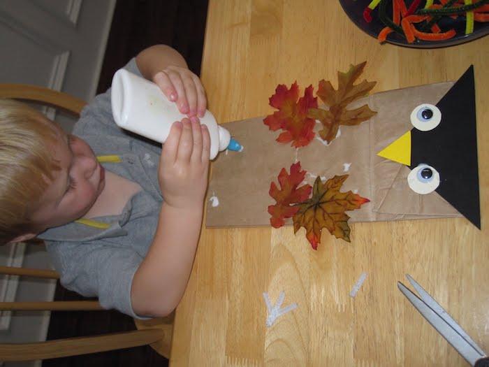 eine große eule aus einer alten braunen papiertüte, ein kind mit einem weißen kleber und ein tosch aus holz, eine bastelanleitung