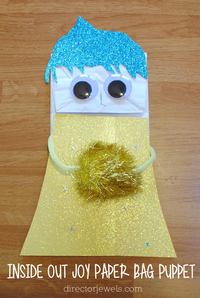 inside out joy, win tisch aus holz und ein mädchen aus papiertüte und mit einem gelben kleid und blaue haare, papiertüten klein falten