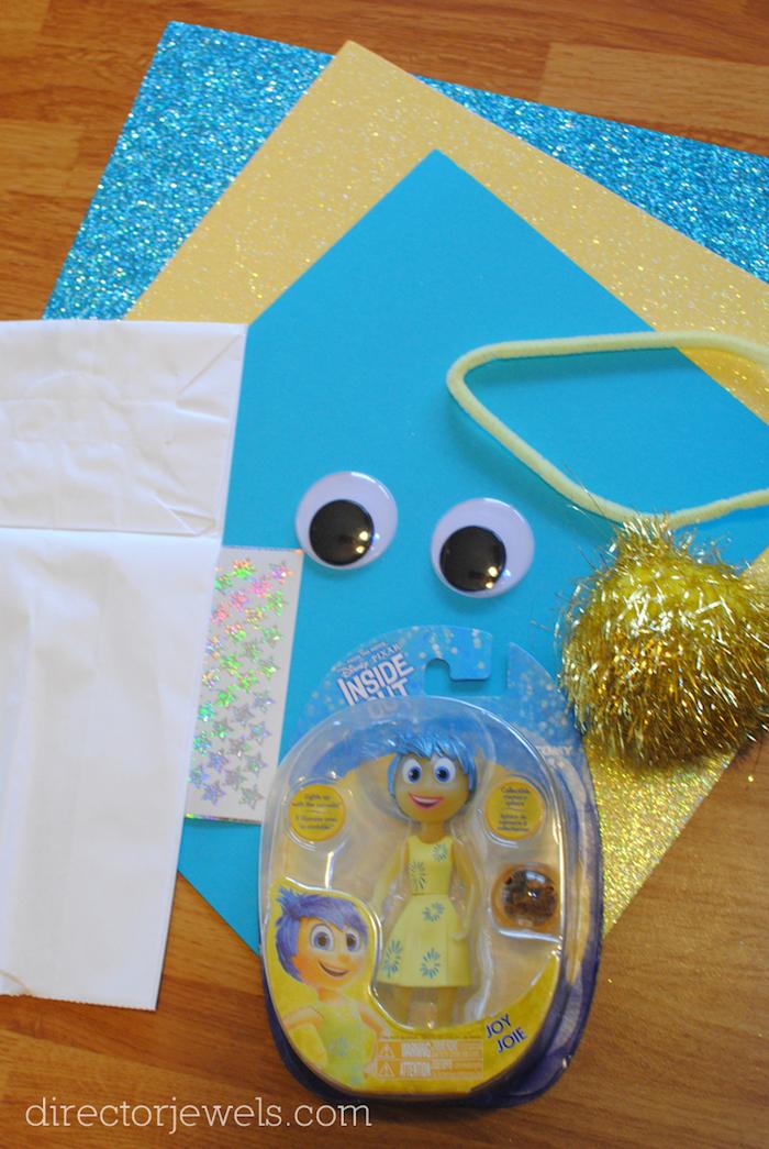 ein tisch aus holz, papiertüten basteln, inside out joy, kleine schwarze augen und blaue und gelbe blätter und ein tisch aus holz