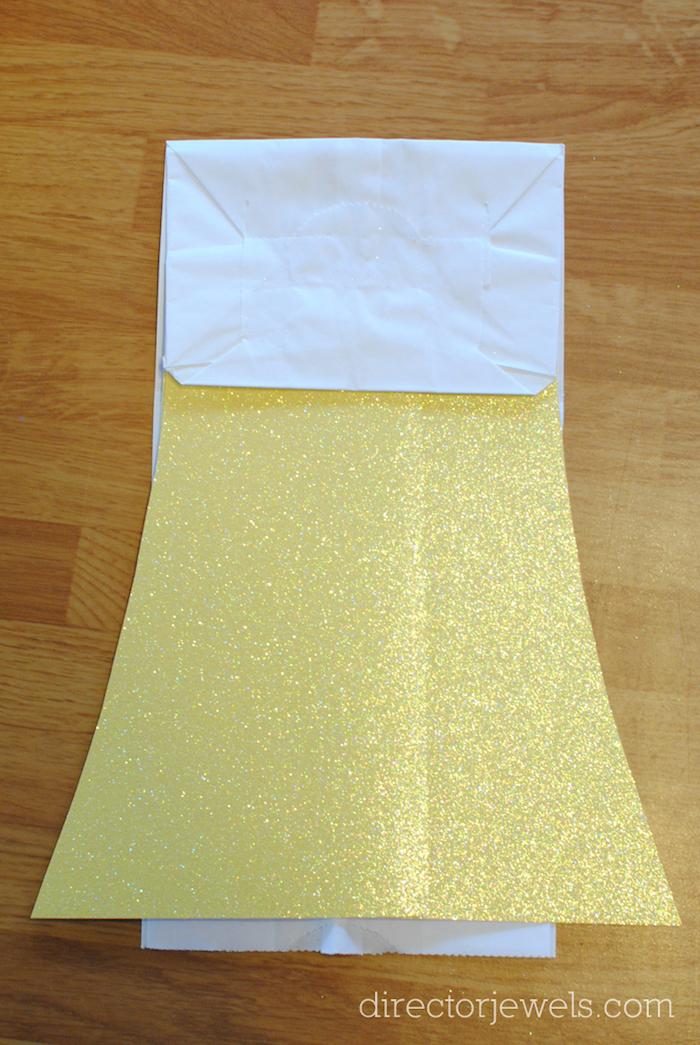 ein tisch aus holz und ein mädchen aus einer weißen papiertüte und mit einem gelben kleid, papiertüten basteln ohne kleben