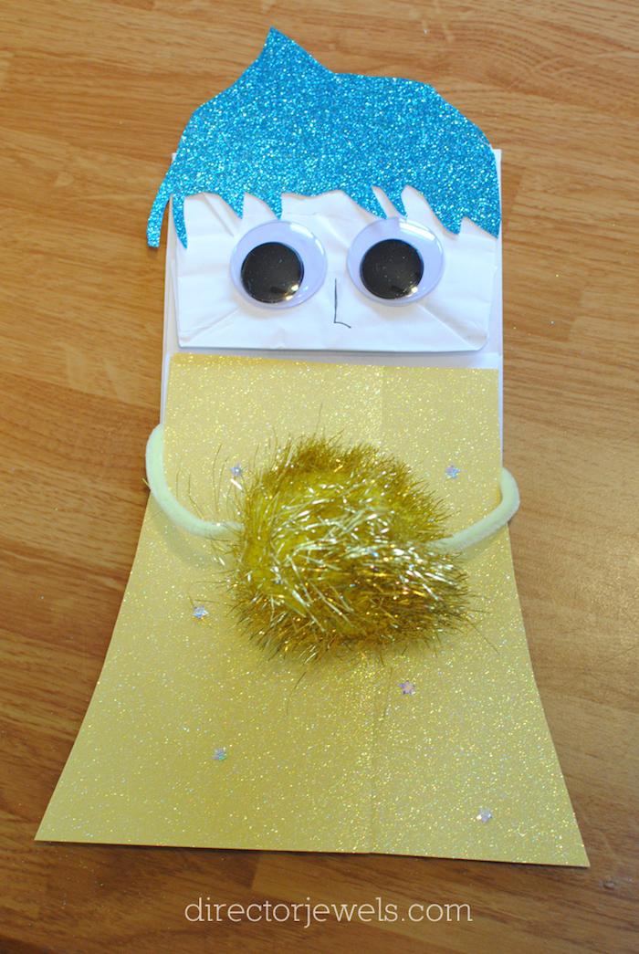 blaue haare und schwarze augen, eintisch aus holz und ein mädchen aus einer kleinen weiße papiertüte und mit einem gelben kleid aus papier, papiertüten falten
