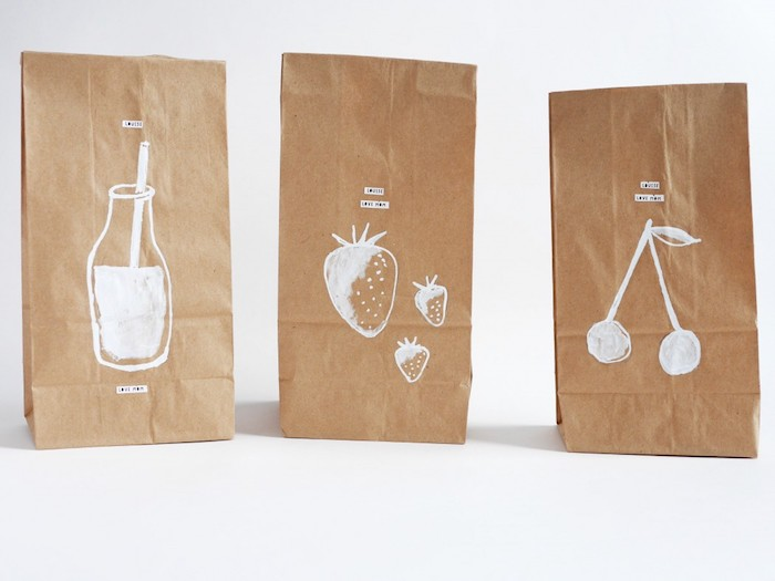 papiertüten braun, drei kleinen tüten aus papier und mit weißen erdbeeren, kirschen und einer weißen flasche, papiertüten basteln
