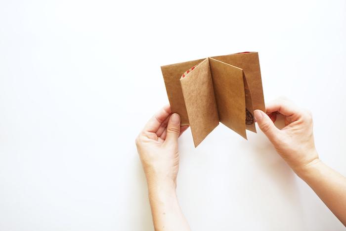 ein kleines braunes buch aus einer alten braunen papiertüte, ein weißer tisch und zwei hände, basteln mit papier