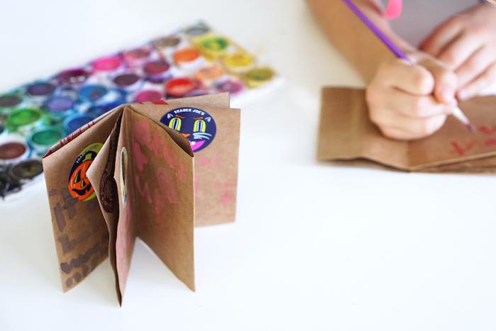 ein kleines braunes buch aus einer kleinen alten braunen tüte und mit einer violetten katze und orangen kürbissen, papiertüten basteln