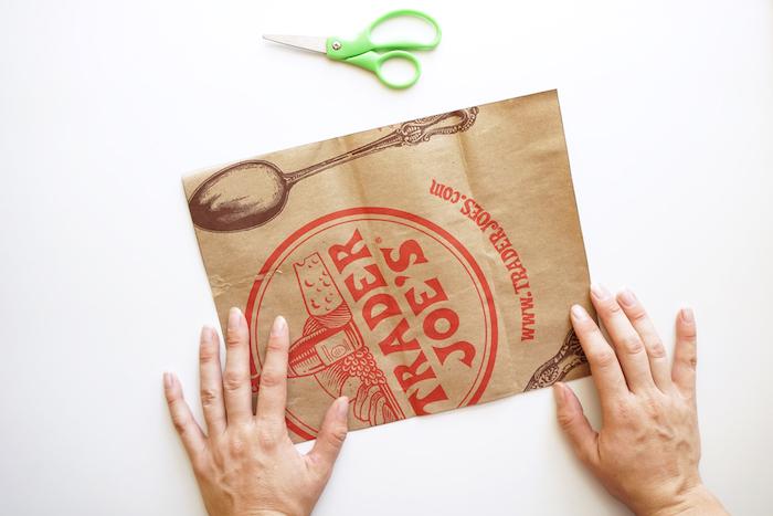 eine kleine grüne schere und zwei hände, altes blatt papier mit einem braunen großen löffel, basteln mit papier