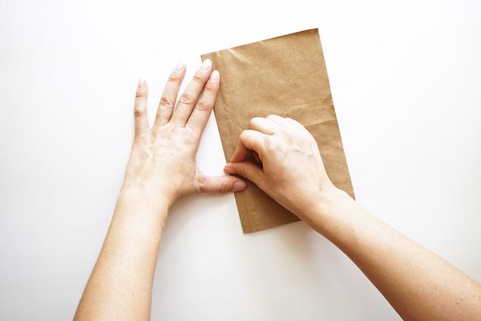 kleine papiertüten falten bastelanleitung, ein weißer tisch und zwei hände, bastelideen für erwachsene