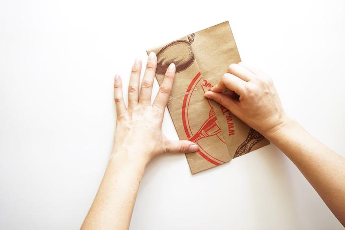 ein brauner löffel und ein kleines braunes altes gefaltetes blatt papier und zwei große hände, eine papiertüte falten anleitung