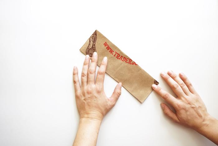 eine papiertüte falten anleitung, ein altes kleines braunes und gefaltetes blatt papier und zwei hände, basteln mit papier