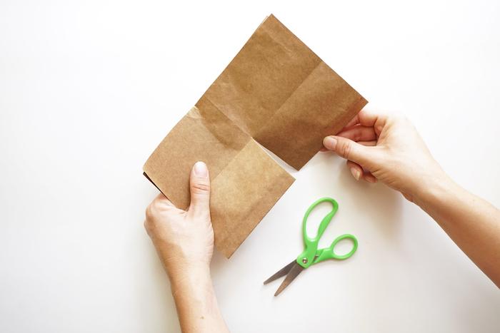 bastelanleitung, eine kleine grüne schere und ein weißer tisch, zwei hände und ein gefaltetes braunes blatt papier