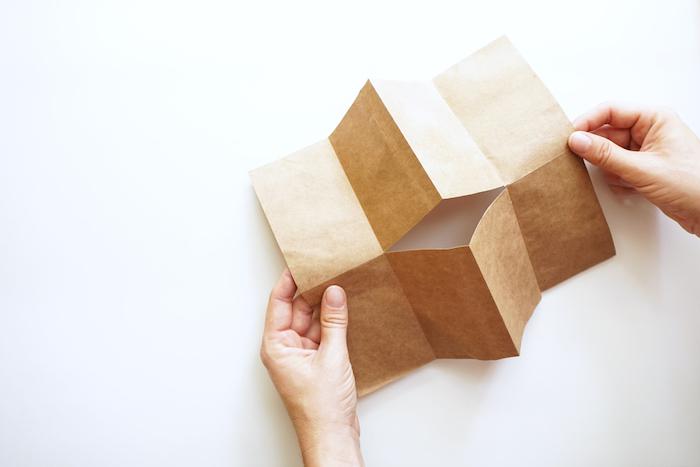 ein gefaltetes altes braunes blatt papier und zwei große hände und ein weißenr tisch, kleine braune papiertüten basteln