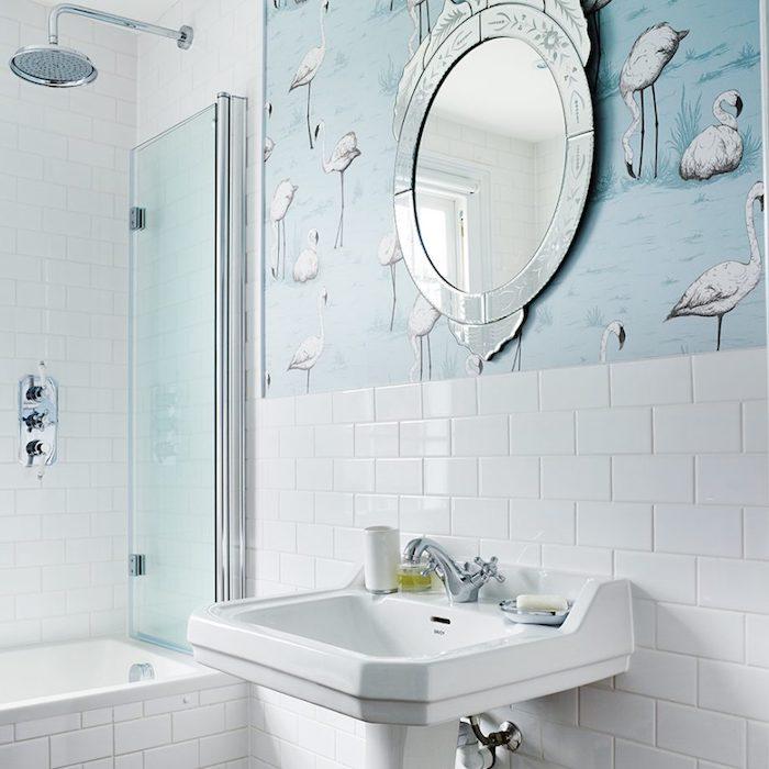 Badezimmer in Weiß und Himmelblau, runder Spiegel mit silbernem Rahmen, weißes Waschbecken